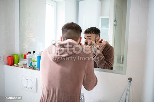 Young man with butterfly tattoo on his hand standing in front of the bathroom mirror and squeezing blackheads on his cheek