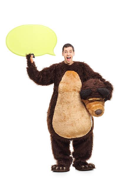 jeune homme dans un costume d'ours tenant un discours bubble - mascotte photos et images de collection