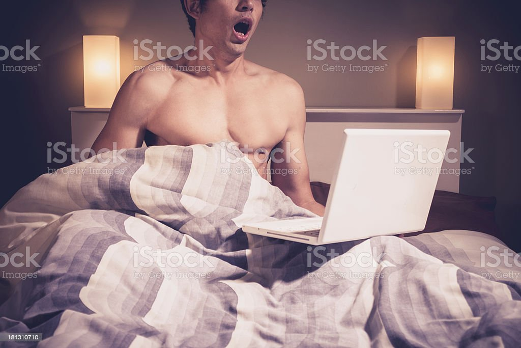 Young man in bed watching pornography on laptop royalty-free stock photo