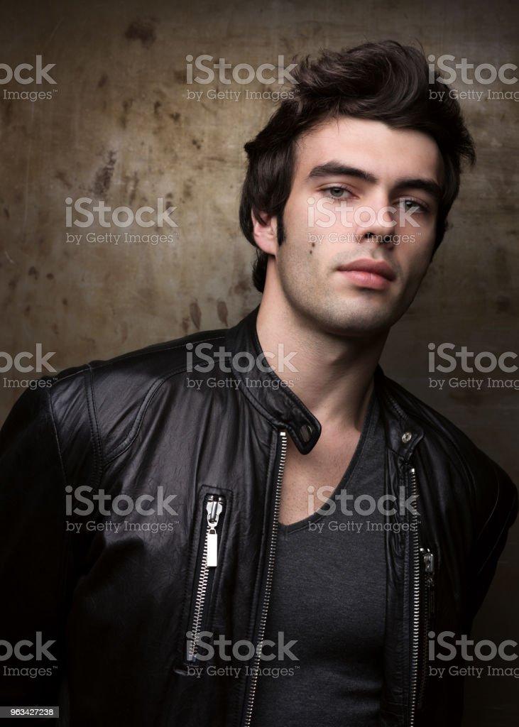 Young man in black leather jacket posing by metal walls. Portrait of the brunette - Zbiór zdjęć royalty-free (Biznes)