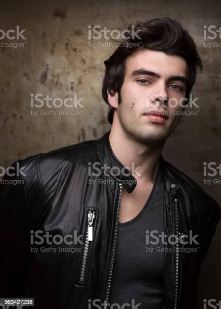 Młody Mężczyzna W Czarnej Skórzanej Kurtce Pozującej Przez Metalowe Ściany Portret Brunetki - zdjęcia stockowe i więcej obrazów Mężczyźni