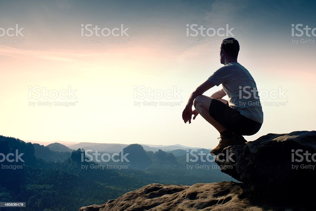 Young man in black pants and shirt  sit on cliff - Royalty-free 2015 Stock Photo