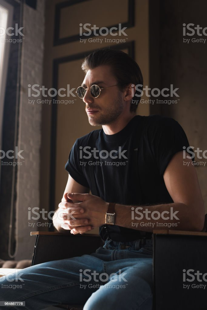 young man in black t-shirt and sunglasses sitting on chair royalty-free stock photo
