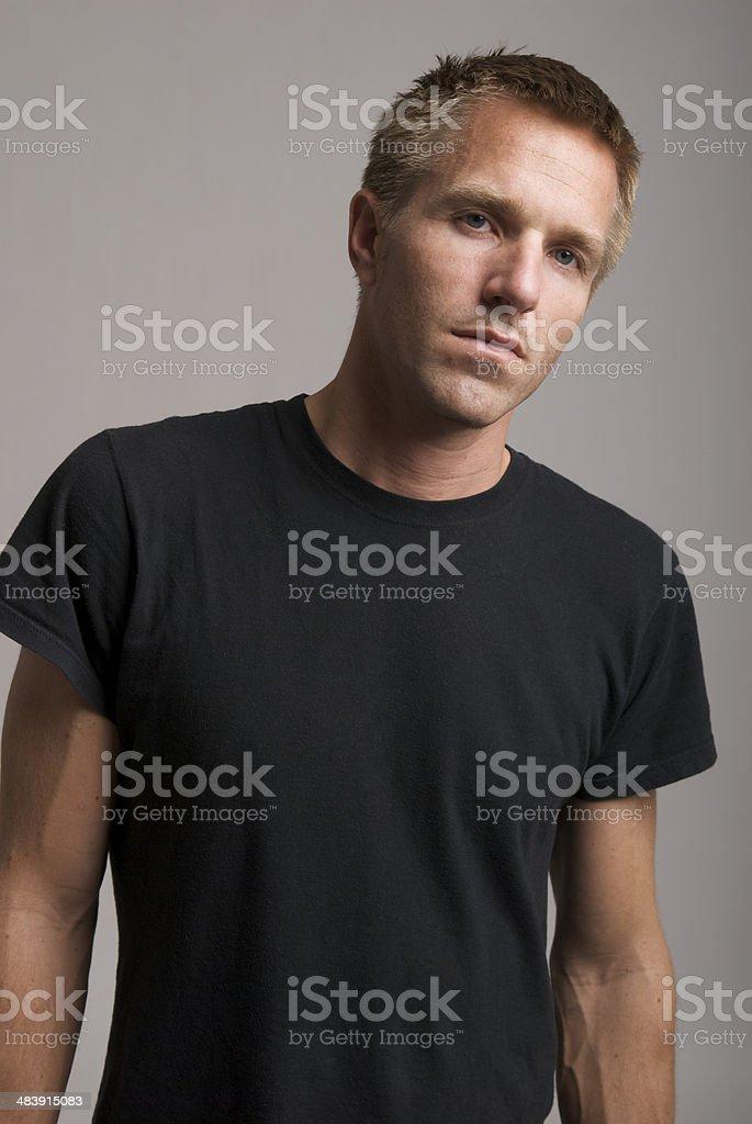 Young Man in Black T-Shirt Looks at Camera Bad Attitude royalty-free stock photo