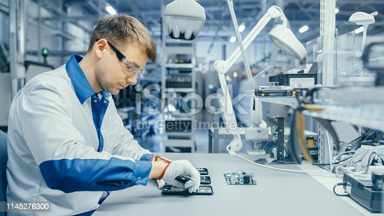 istock Young Man in Blue and White Work Coat is Using Plier to Assemble Printed Circuit Board for Smartphone. Electronics Factory Workers in a High Tech Factory Facility. 1145276300
