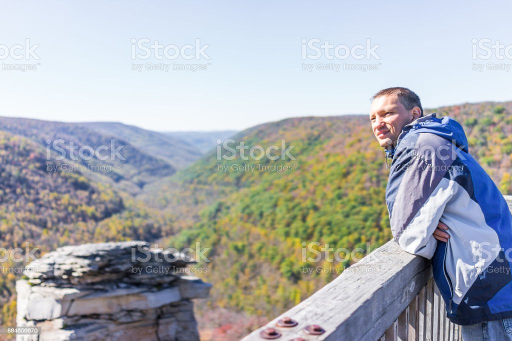 Young man in blue jacket looking at canaan valley mountains in Blackwater falls state park in West Virginia during colorful autumn fall season with yellow foliage on trees, rock cliff at Lindy Point stock photo