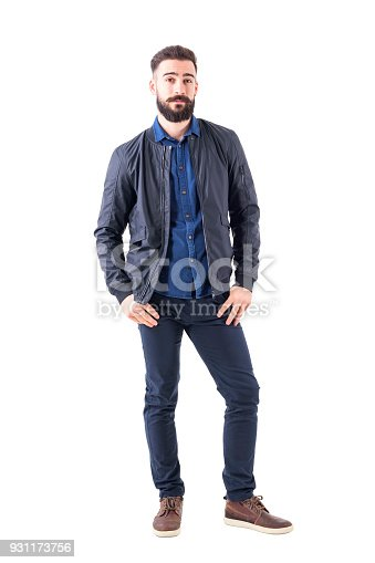 931173966istockphoto Young man in blue shirt and bomber jacket with thumbs in pockets looking at camera 931173756