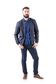 istock Young man in blue shirt and bomber jacket with thumbs in pockets looking at camera 931173756