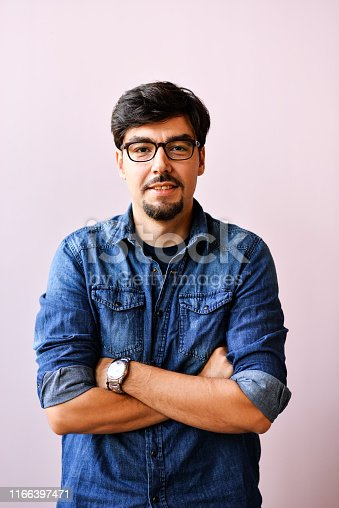 Attractive young man in blue shirt,and glasses smiling over pink background