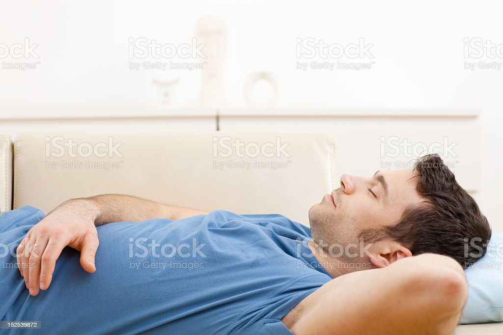Young man in blue shirt sleeping on a couch stock photo