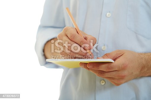 1175668510 istock photo Young man in blue shirt taking notes on white background 473326372