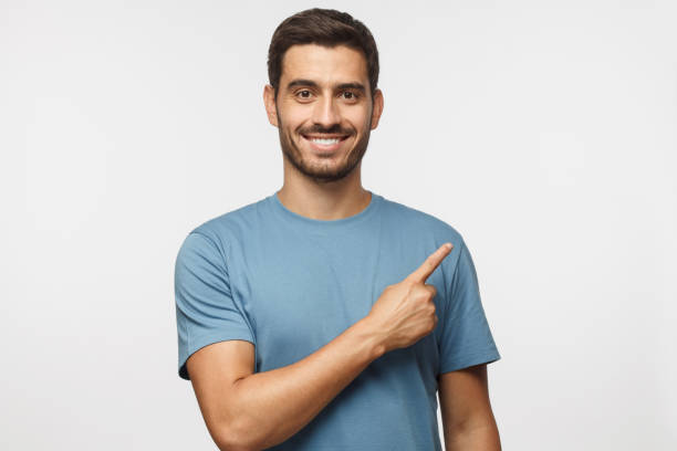 Young man in blue t-shirt pointing right with his finger isolated on gray background stock photo