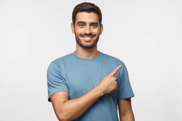 年輕男子在藍色 t恤指向右與他的手指在灰色背景下隔離 - 瞄準 個照片及圖片檔