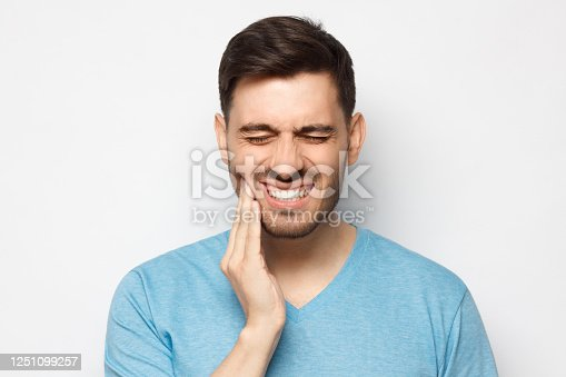 Young man in blue tshirt touching his face and closing eyes with expression of horrible suffer from aching tooth, isolated on gray background