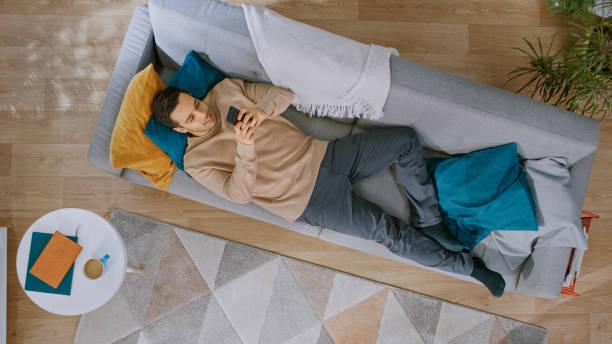 Junger Mann in braunen Pullover und graue Jeans kommt und liegt unten auf einem Sofa, mit einem Smartphone. Er ist glücklich und lächelt. Gemütliches Wohnzimmer mit modernem Interieur mit Pflanzen, Tisch und Holzboden. Top-Ansicht. – Foto