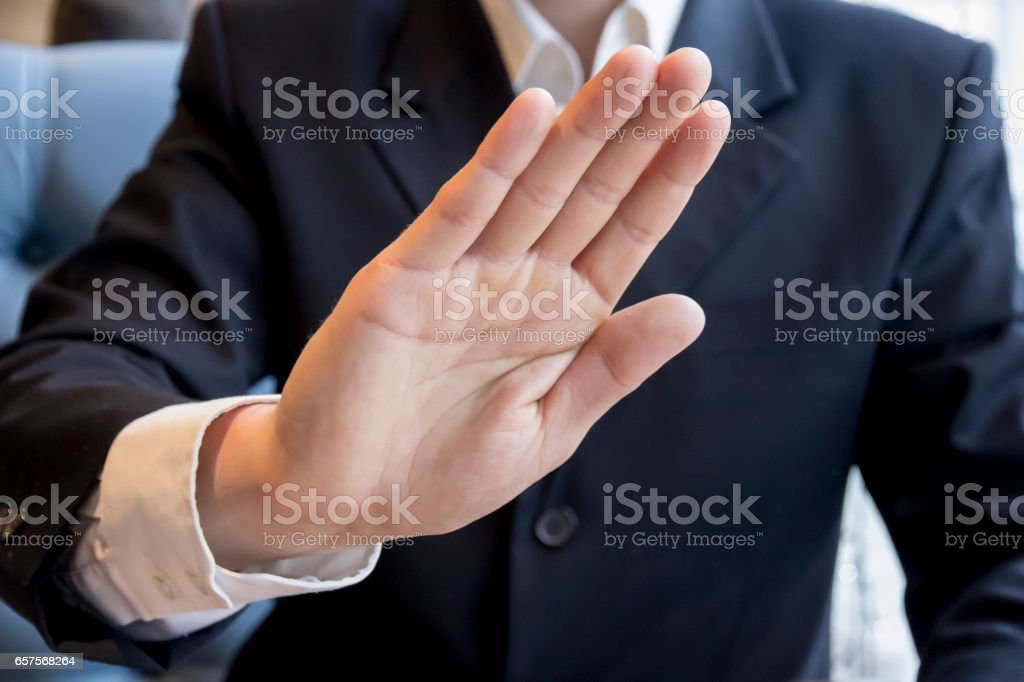 Young man in business suit in cafe shows hand stop sign stock photo