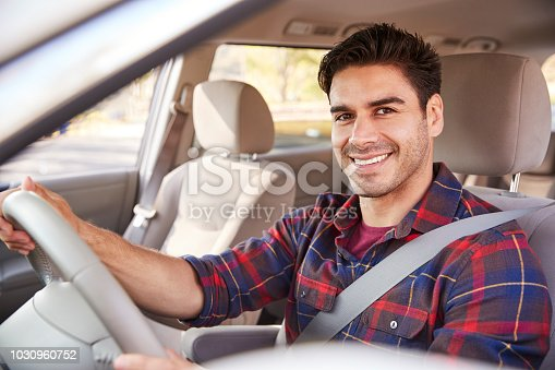 istock Young man in car driving seat looking to camera, portrait 1030960752