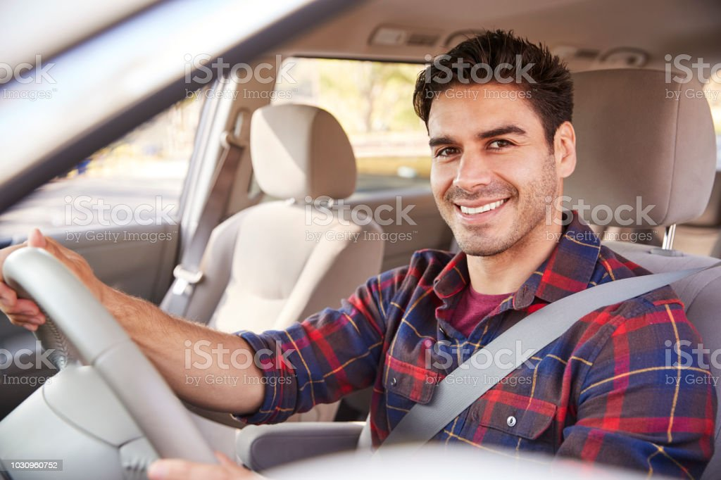Young man in car driving seat looking to camera, portrait stock photo