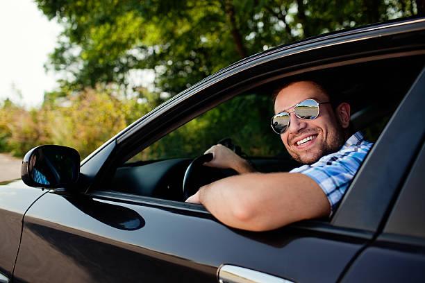 junger mann lächelnd in auto - 1m coupe stock-fotos und bilder