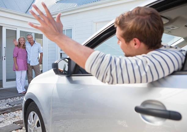 jeune homme dans la voiture au revoir en agitant leurs parents - homme faire coucou voiture photos et images de collection