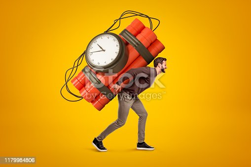 Young man in casual clothes carrying big red dynamite stick time bomb on his back on yellow background. People and objects. Explosive materials. Time bomb ready to explosion.