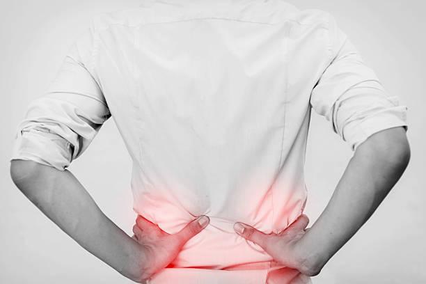 Młody człowiek w koszuli na biura o ból biodra – zdjęcie