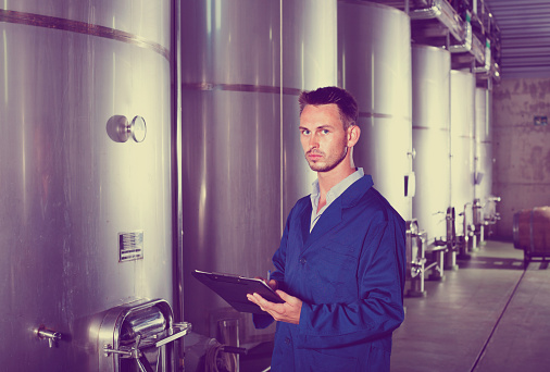 istock Young man in coat taking notes on wine factory 1077557812