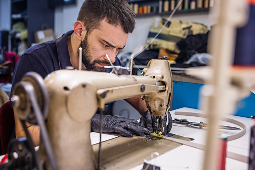 Young man running small business wearing protective gloves and using sewing machine, focused on the needle, crafts repair workshop