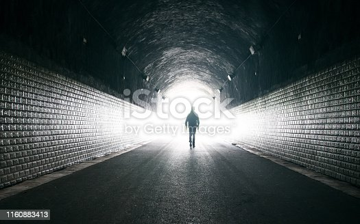 Young man in dark tunnel