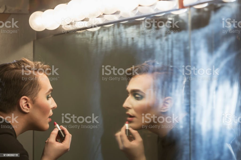 Young man in dressing room applying make-up - drag queen stock photo