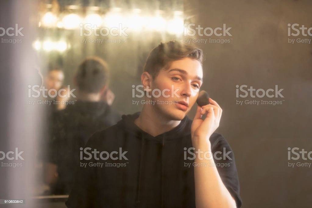 Young man in dressing room applying make-up stock photo