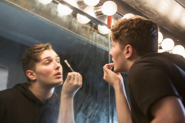 junger mann in umkleidekabine schminken - anzieh nacht stock-fotos und bilder
