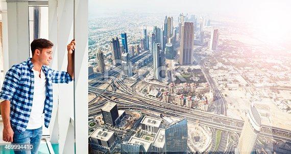 Young man in Dubai looking through a window. Shoot from Istockalypse Dubai 2015.