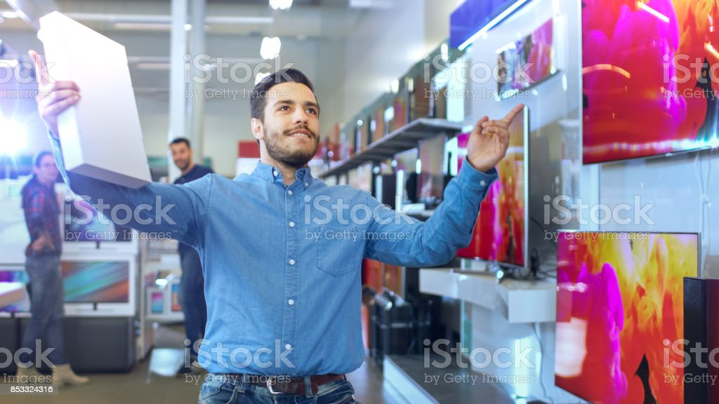 Young Man in Electronics Store Purchased Latest Model of the Tablet Computer and Dances Happily with the Box. Bright and Modern Store Has all the Latest Devices in Store. stock photo