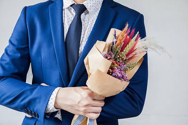 junger mann in eleganten anzug hält hipster handgemachten bouquet - hochzeitsanzug herren stock-fotos und bilder