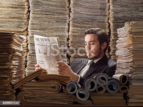 istock Young Man In Formal Wear Doing Research In Printed Media Library 839901240