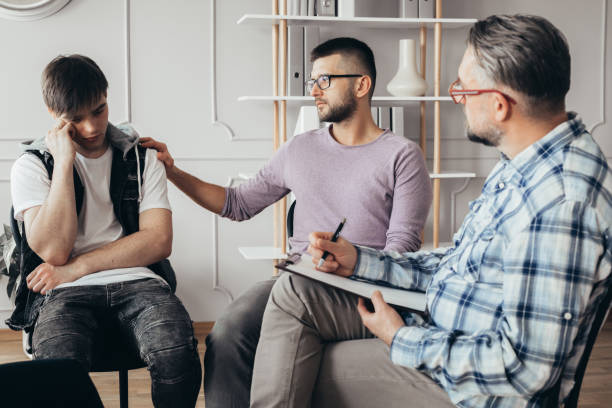 Young man in glasses comforting his depressed friend during meeting with counselor Young man in glasses comforting his depressed friend during meeting with counselor post traumatic stress disorder stock pictures, royalty-free photos & images