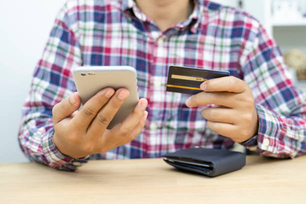 young man in glasses shopping online with credit card using smart phone at home. Indoor. stock photo