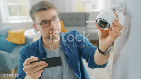 istock Young Man in Glasses Wearing a Blue Shirt is Adjusting a Modern Wi-Fi Surveillance Camera with Two Antennas on a White Wall at Home. He's Checking the Video Feed on his Smartphone. 1212406152