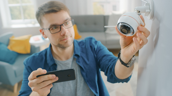 Young Man in Glasses Wearing a Blue Shirt is Adjusting a Modern Wi-Fi Surveillance Camera with Two Antennas on a White Wall at Home. He's Checking the Video Feed on his Smartphone.