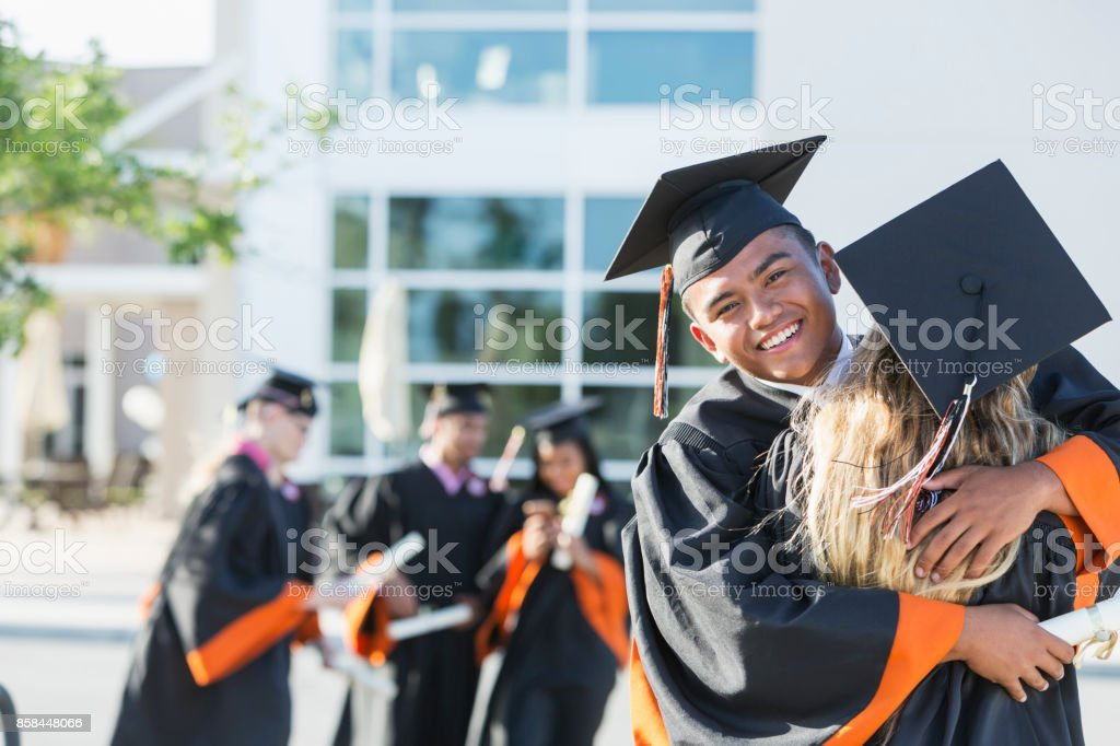 Young Man In Graduation Cap And Gown Embracing Friend Stock Photo ...