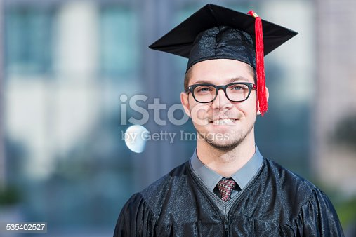 Portrait of a young man wearing a black graduation cap and gown, standing outdoors.  He is wearing eyeglasses, smiling at the camera.