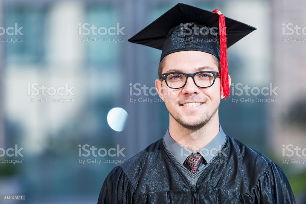 Young man in graduation cap and gown stock photo