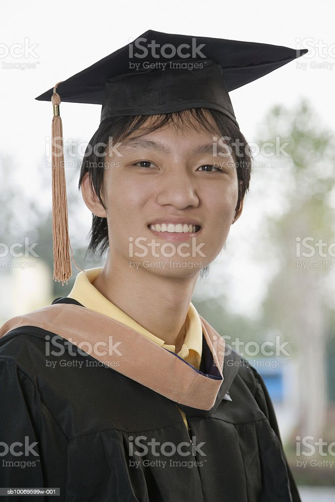Young man in graduation gown smiling, close-up, portrait foto de stock libre de derechos