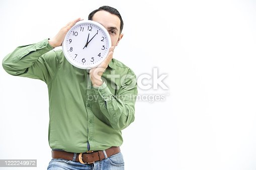 Young man in green is waiting, holding clock in front of his face over white background. Time is passing concept.