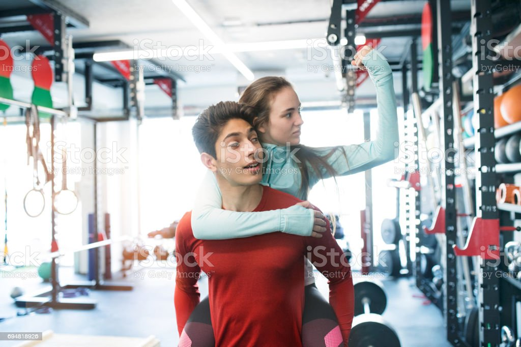 Young man in gym carrying woman on his shoulders. royalty-free stock photo