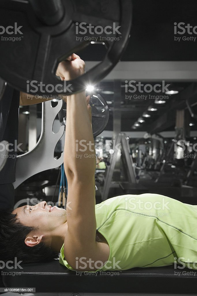 Young man in gym lifting weight, side view photo libre de droits