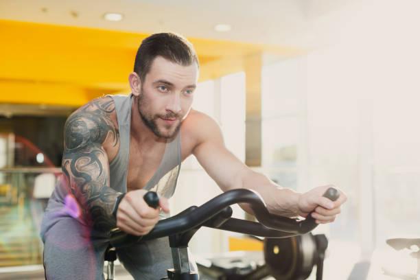 junger mann im fitnessstudio fahrt schreibwaren fahrrad - laufende tattoos stock-fotos und bilder
