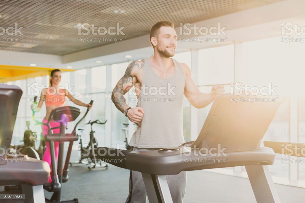 Young man in gym run on treadmill stock photo