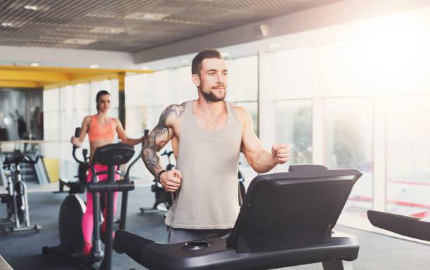junger mann im fitnessstudio auf dem laufband laufen - laufende tattoos stock-fotos und bilder